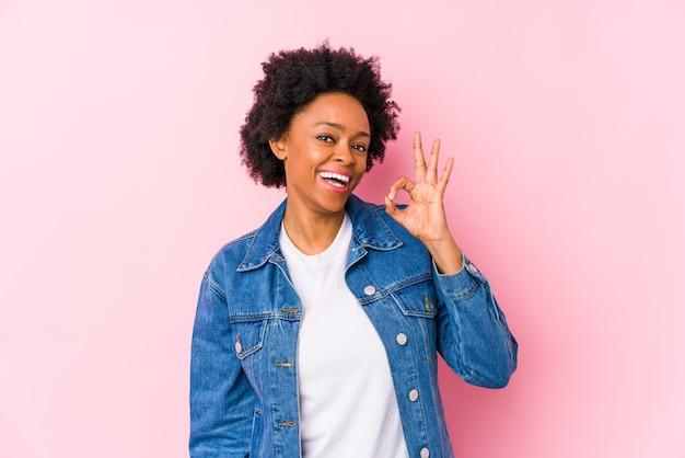 孤立したピンクの背景に対して若いアフリカ系アメリカ人の女性は目をまばたきし、手で大丈夫なジェスチャーを保持します。