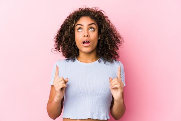 開いた口で逆さまに指しているピンクの背景に対して若いアフリカ系アメリカ人女性。