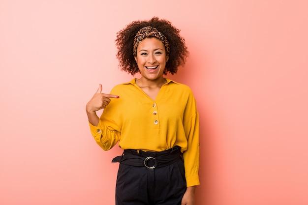 Молодая афроамериканка против розовой стены лица, указывая рукой на рубашку копией пространства, гордый и уверенный