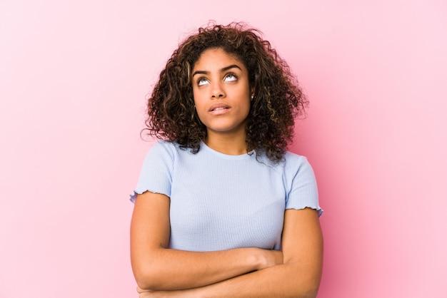 Молодая афро-американская женщина против розовой стены утомляла повторяющейся задачи.