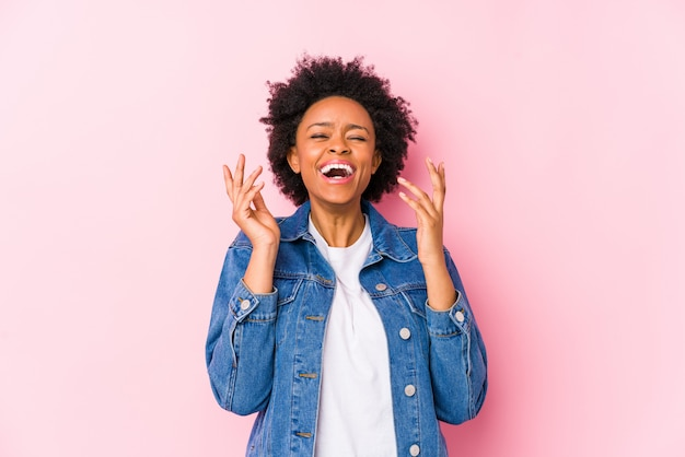 Young african american woman against a pink backgroound isolated joyful laughing a lot. happiness concept.