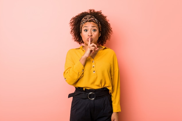 Young african american woman against a pink background keeping a secret or asking for silence.