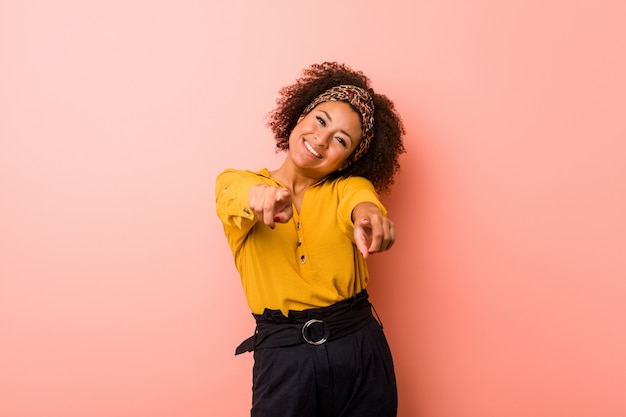 Young african american woman against a pink  cheerful smiles pointing to front.