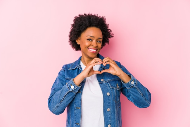 Young african american woman against a pink isolated smiling and showing a heart shape with hands.