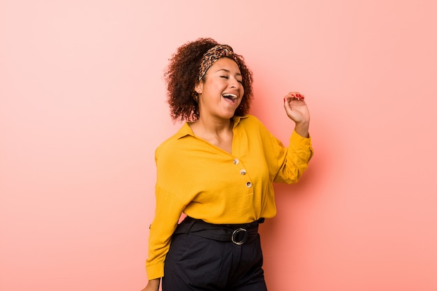 Young african american woman against a pink wall dancing and having fun.
