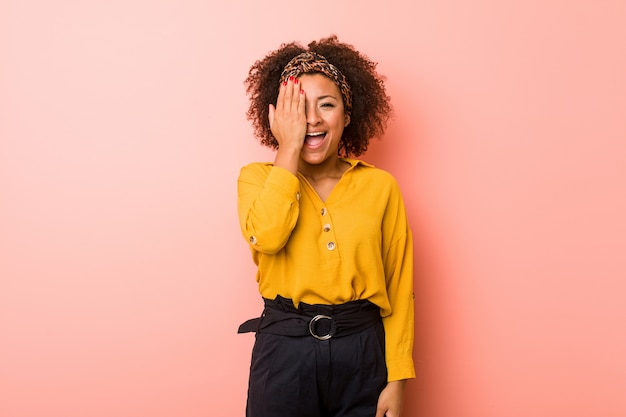 Young african american woman against a pink wall having fun covering half of face with palm.