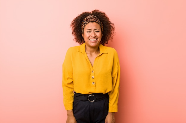 Young african american woman against a pink wall laughs and closes eyes, feels relaxed and happy.