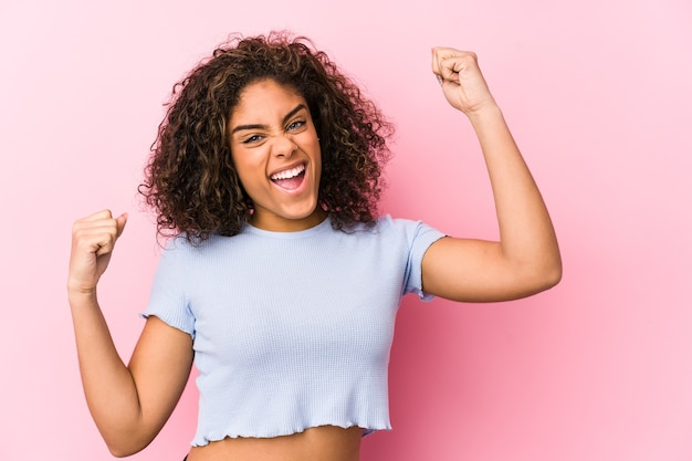 Young african american woman against a pink wall raising fist after a victory, winner concept.
