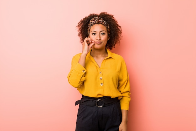 Young african american woman against a pink wall with fingers on lips keeping a secret.