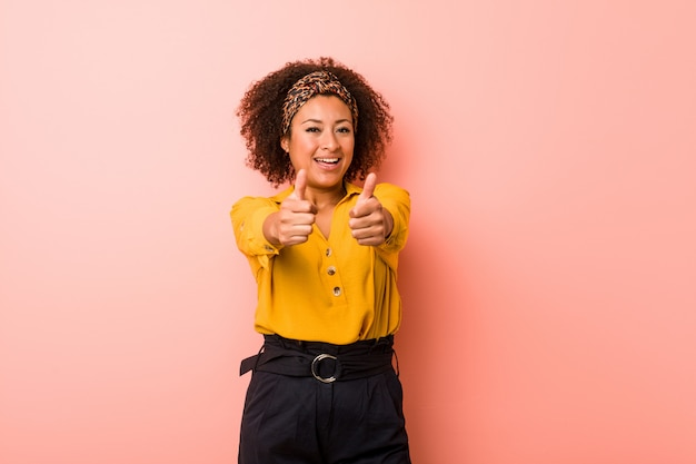 Young african american woman against a pink wall with thumbs ups, cheers about something, support and respect concept.