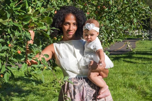 Молодая афро-американская женщина и ее дочь улыбается, гуляя в летнем парке.