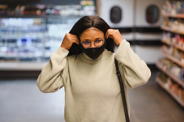 Молодая афроамериканка в торговом центре в новом нормальном состоянии после covid-19 - счастливая и красивая темнокожая девушка в маске держит сумки с покупками в магазине модной красоты