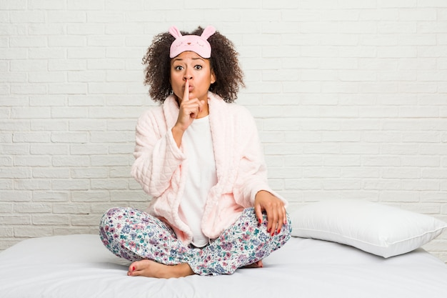 Young african american woman in the bed wearing pijama keeping a secret or asking for silence.