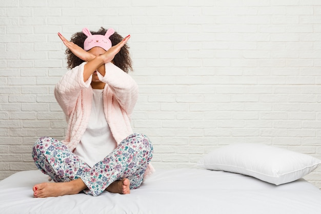 Young african american woman in the bed wearing pijama keeping two arms crossed, denial concept.