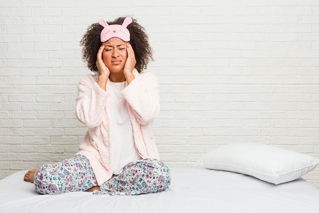 Young african american woman in the bed wearing pijama touching temples and having headache.