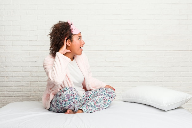 Young african american woman in the bed wearing pijama trying to listening a gossip.