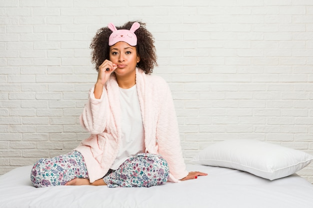Young african american woman in the bed wearing pijama with fingers on lips keeping a secret.