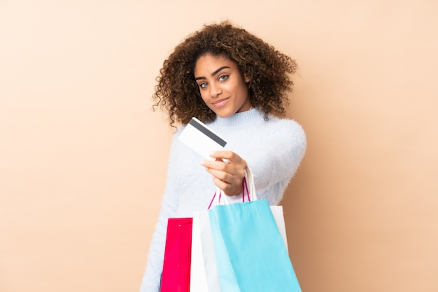 Young african american woman on beige wall holding shopping bags and a credit card