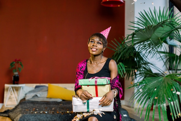 Young african american woman in a birthday hat holding gifts boxes