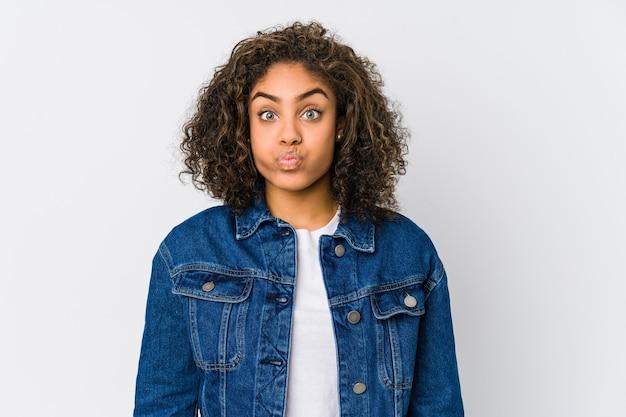 Молодая афро-американская женщина дует щеки, утомленное выражение. концепция выражения лица.