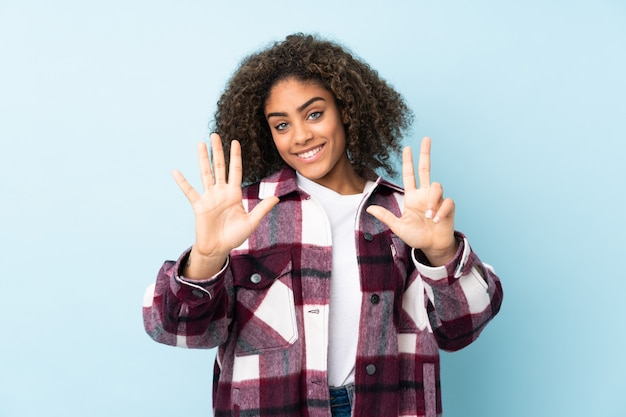 Young african american woman on blue wall counting eight with fingers