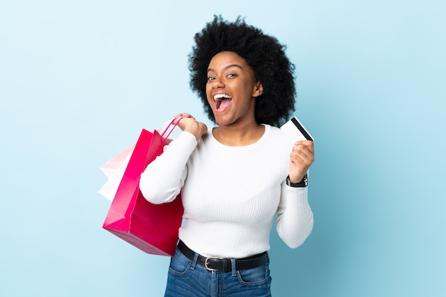 Young african american woman on blue wall holding shopping bags and a credit card