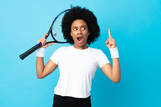 Young african american woman on blue wall playing tennis and pointing up