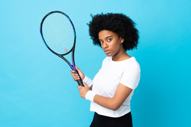 Young african american woman on blue wall playing tennis