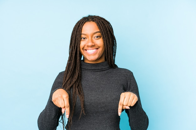 Young african american woman on blue wall points down with fingers, positive feeling.