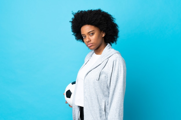 Young african american woman on blue wall with soccer ball