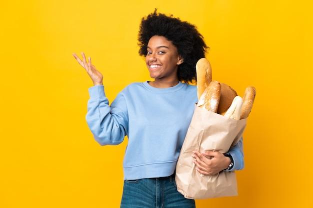 Молодая афро-американская женщина, покупающая что-то хлеб, изолирована на желтом фоне, протягивая руки в сторону, приглашая приехать