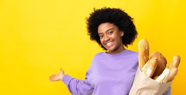 노란색 배경에 고립 된 빵을 구입하는 젊은 아프리카 계 미국인 여자가 와서 초대하기 위해 손을 옆으로 확장