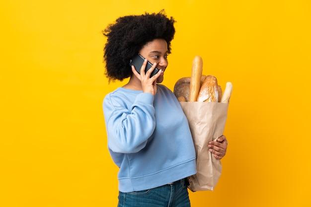 Молодая афроамериканская женщина покупает что-то хлеб, изолированные на желтом фоне, разговаривая с кем-то по мобильному телефону