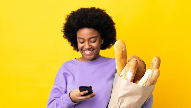 Молодая афроамериканец женщина, покупая что-то хлеб, изолированных на желтом фоне, отправив сообщение с мобильного телефона