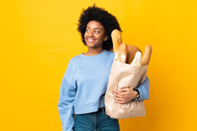 見上げながらアイデアを考えて黄色の背景に分離されたパンを買う若いアフリカ系アメリカ人女性