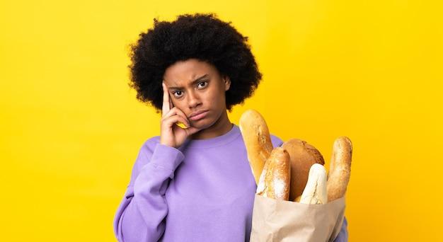 アイデアを考えて黄色の背景に分離されたパンを買う若いアフリカ系アメリカ人女性