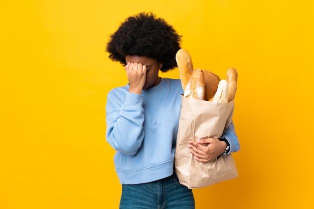 두통으로 노란색 배경에 고립 된 빵을 구입하는 젊은 아프리카 계 미국인 여자