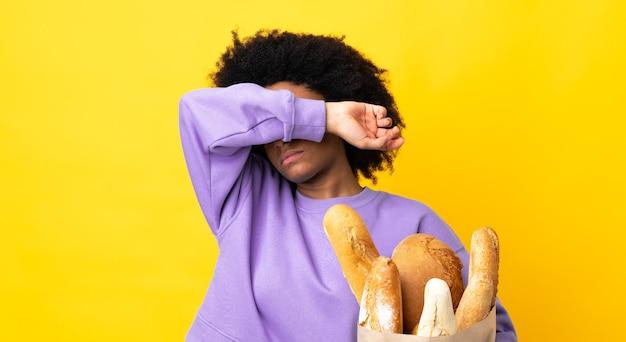 Молодая афроамериканская женщина покупает что-то хлеб, изолированные на желтых конических глазах руками