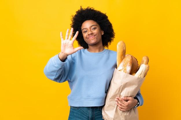 Молодая афро-американская женщина покупая что-то хлеб изолированный на желтом цвете подсчитывая 5 с пальцами
