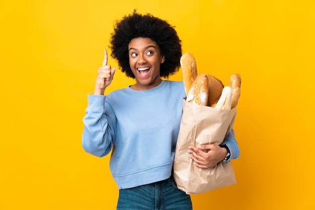 손가락을 들어 올리는 동안 솔루션을 실현하려는 노란색에 고립 된 빵을 구입하는 젊은 아프리카 계 미국인 여자