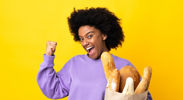 勝利を祝っている黄色の壁に分離された何かのパンを買う若いアフリカ系アメリカ人女性