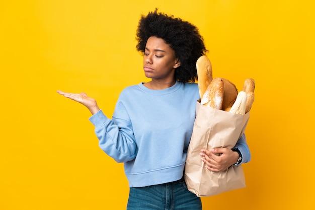 의심의 여지가 copyspace 들고 노란색 벽에 고립 된 빵을 구입하는 젊은 아프리카 계 미국인 여자
