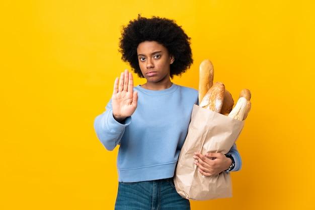 중지 제스처를 만드는 노란색 벽에 고립 된 빵을 구입하는 젊은 아프리카 계 미국인 여자