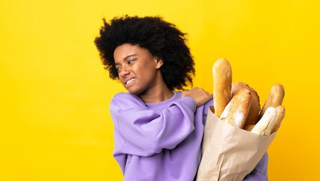 Молодая афро-американская женщина покупая что-то хлеб изолированный на желтой стене страдая от боли в плече для того чтобы сделать усилие