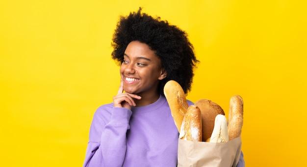Молодая афро-американская женщина покупая что-то хлеб изолированный на желтой стене думая идея пока смотрящ вверх