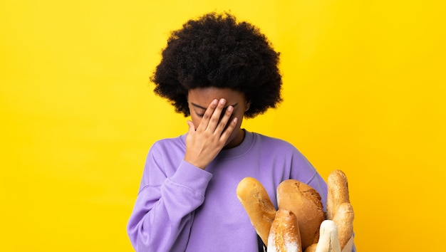 Young african american woman buying something bread isolated on yellow background with tired and sick expression