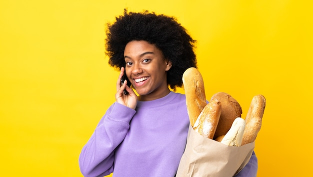 Young african american woman buying something bread isolated on yellow background
