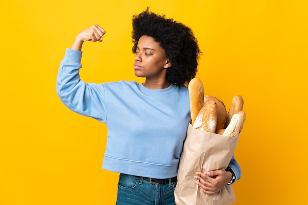 Young african american woman buying something bread isolated on yellow doing strong gesture