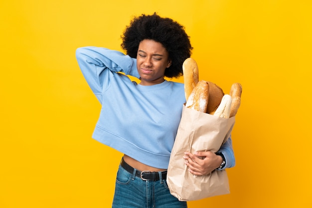 Young african american woman buying something bread isolated on yellow with neckache