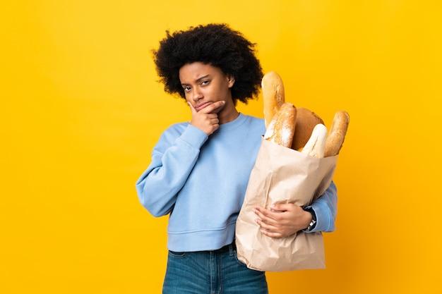 Молодая афро-американская женщина покупая что-то хлеб на желтой стене и думая